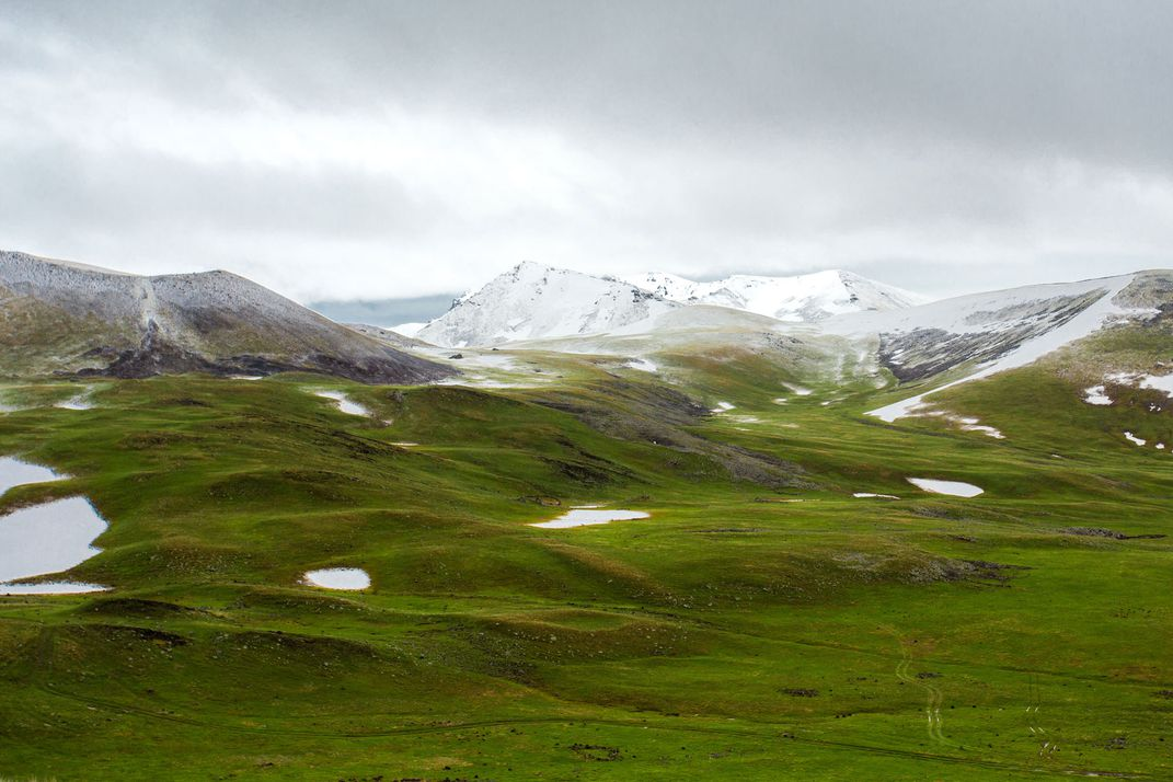 A rich, mossy valley leads up to snow capped mountains.