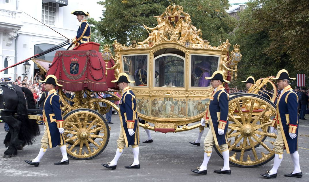 Men dressed in royal garb walk alongside an elaborate coach, gilded in gold with large wheels. On the side of the coach, a triptych depicts a white woman on a throne, being offered gifts by half-naked black people, who bow or look downward