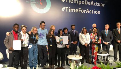 Sara Cognuck (center) shows the Declaration on Children, Youth and Climate Action.