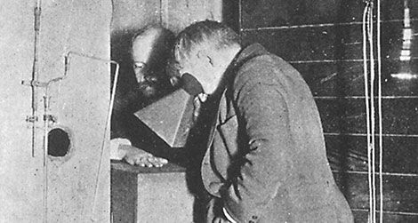 Thomas Edison examines Clarence Dally's, his assistant, hand thru a fluoroscope of his own design.