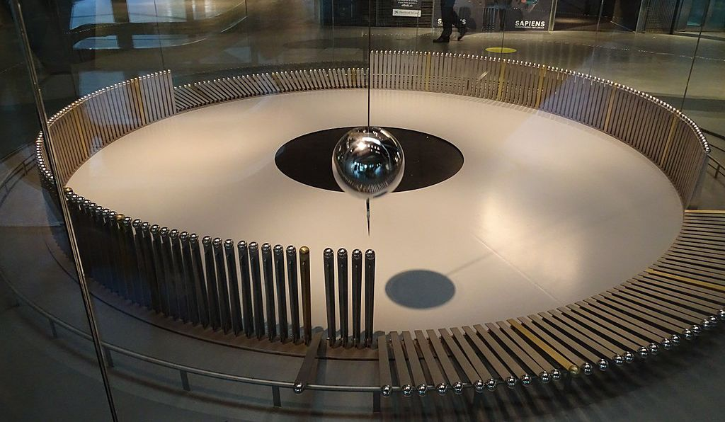 A Foucault-inspired pendulum apparatus at the CosmoCaixa museum in Barcelona, Spain. As the path of the pendulum shifts due to Earth's rotation, the bob will gradually knock over all of the vertical rods around the circle's circumference.