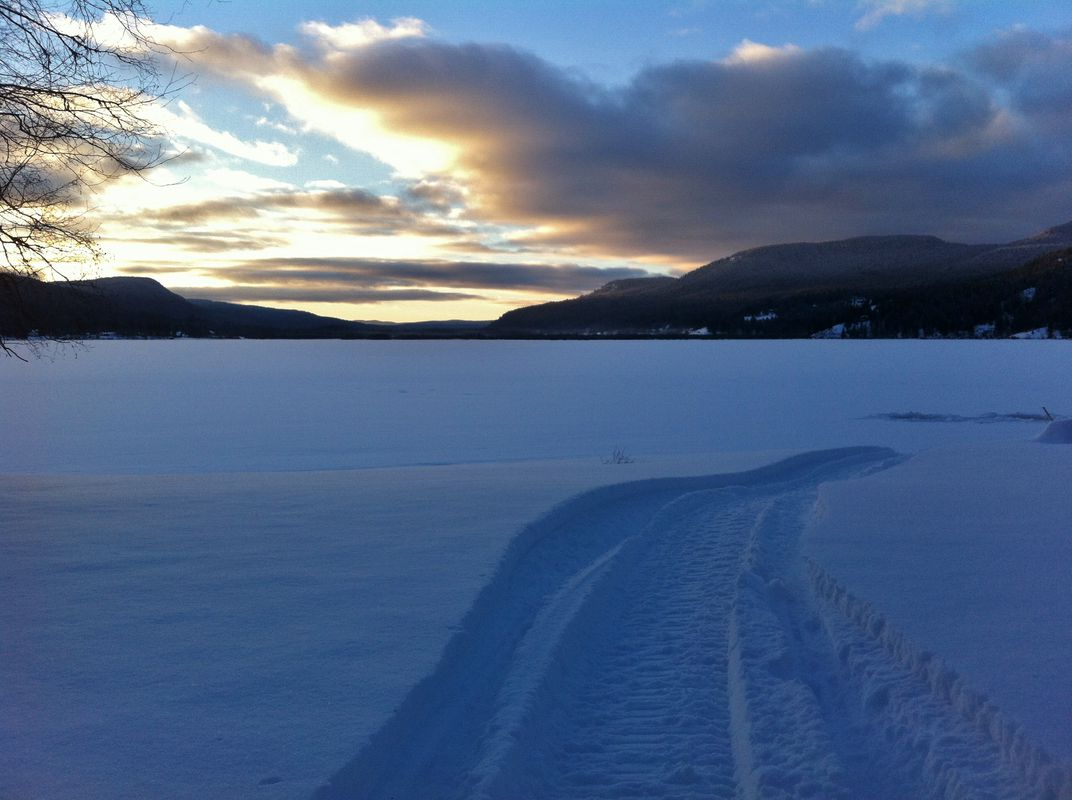 Snowmobile tracks in the snow across a frozen Canim Lake