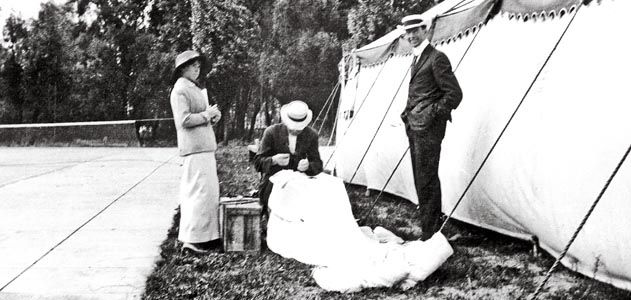 Glenn Martin (standing). By 1913 Martin was taking credit for Broadwick's invention, and the following year he patented it. Here, he and Tiny watch Broadwick stitch up the canopy of a parachute.