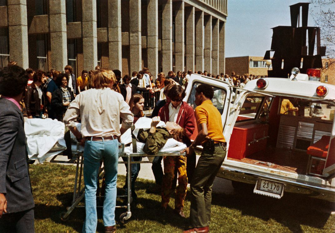 A student on a stretcher is wheeled to an ambulance