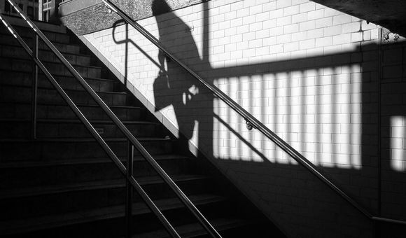 An old woman walks up a stairwell of the NYC Subway in Manhattan.  Her shadow is cast on the wall from the Winter Sun.