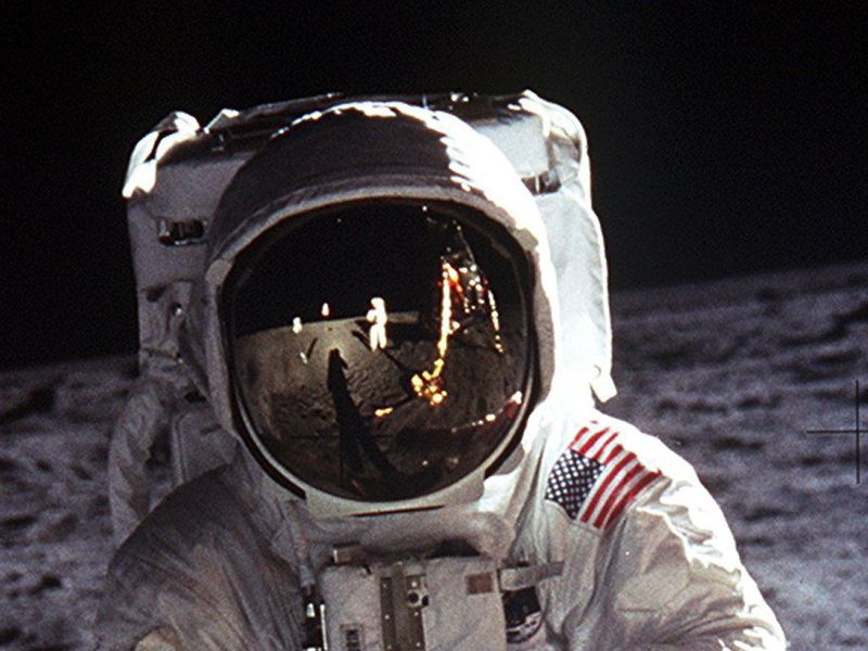 Astronaut Buzz Aldrin wears a large helmet and white space suit while standing on the moon. The American flag, Neil Armstrong and more of the moon is reflected in his helmet. The moon's rocky, gray surface makes up the background.