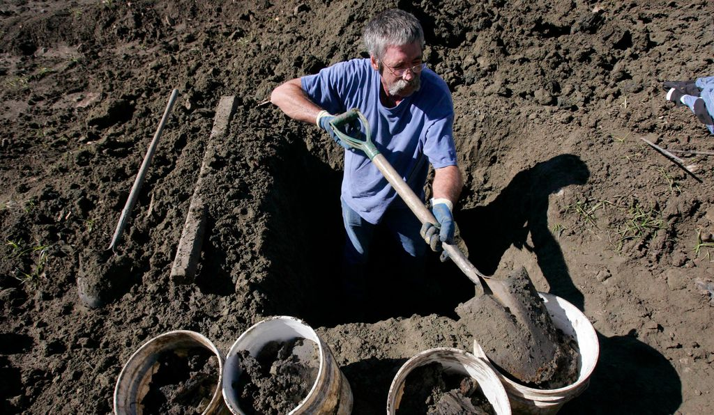 A man fills up buckets with dirt while hunting for diamonds at Crater Diamonds State Park in Murfreesboro, Arkansas.