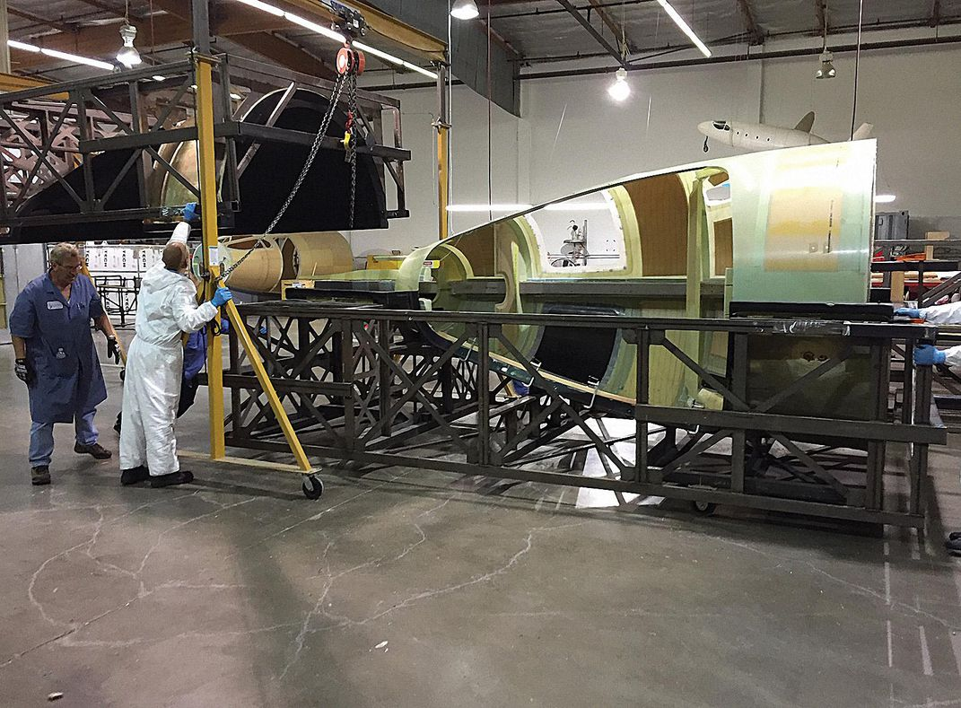 people removing fuselage from a mold