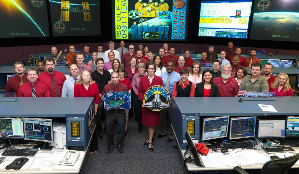 In a group portrait of flight controllers for space shuttle <i>Atlantis</i> mission STS-132 in 2010, Ridings is front and center, holding the mission patch.
