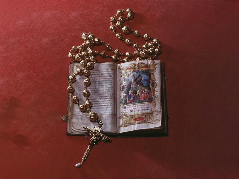 On a red background, an open illuminated Bible with colorful illustrations depicting Jesus kneeling and praying, encircled by a golden rosary with large round beads and a cross decorated with pearls and a golden figure of Jesus crucified on its end