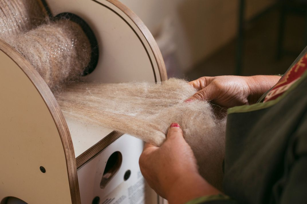 Two hands pull out freshly cleaned wool from a carding machine.