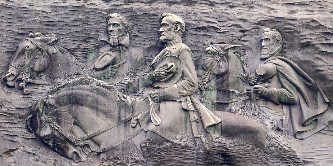 A stone carving of three men on horseback, carved into the side of a granite mountain face