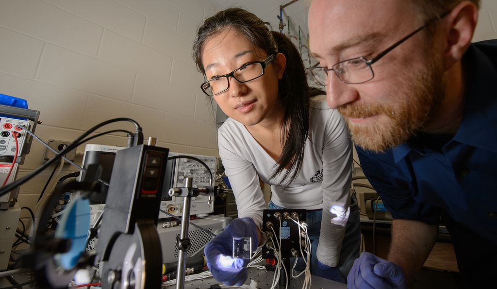 Assistant Professor Richard Lunt and Yimu Zhao, a doctoral student, test the transparent solar material at Michigan State University.