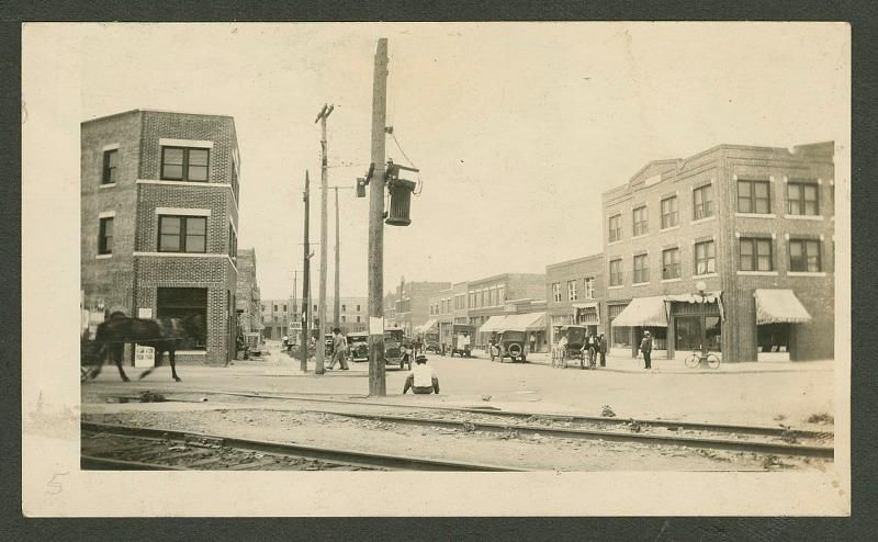 A yellow-toned black and white image of a cross-street, with a horse and carriage on the left, a Black person sitting in center frame, and many businesses and storefronts lining a city street