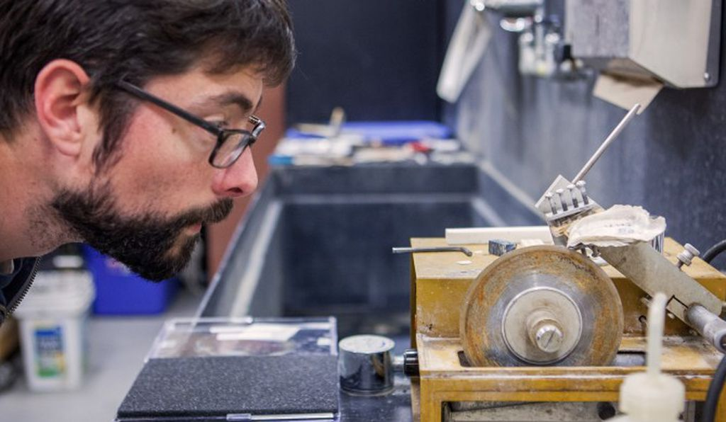 At his lab, Stephen Durham uses a diamond saw to slice through an oyster shell.