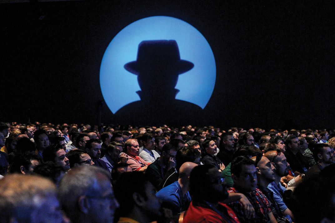 people sitting while an image of a silhouette in a hat is projected
