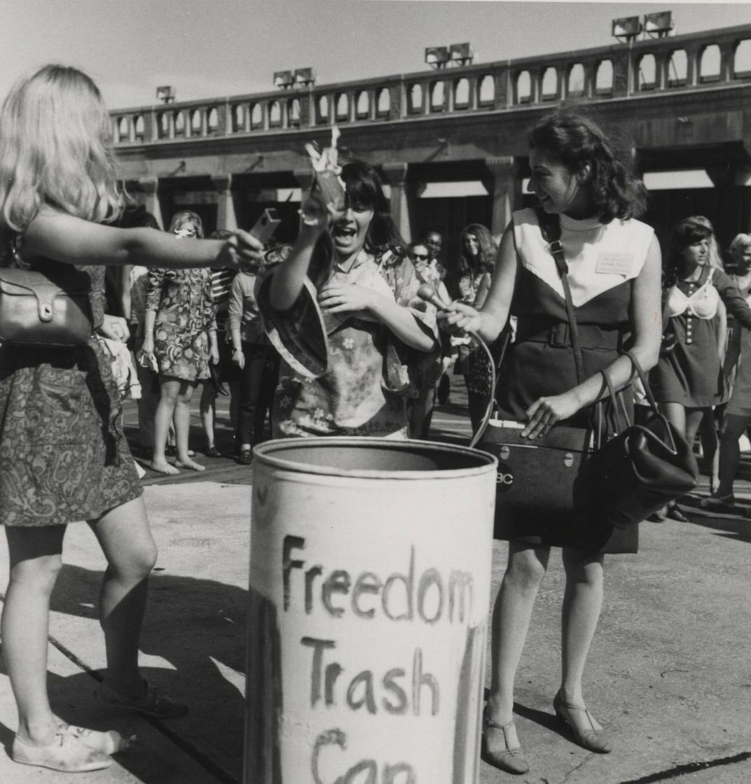 Women of the 1968 Miss America Pageant Protest throw feminine objects into a Freedom Trash Can