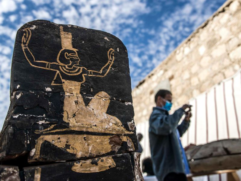 Tourist stands next to wooden coffin unearthed at Saqqara