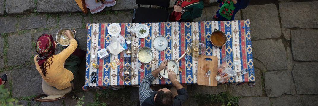 Seen from above, a table covered with a blue and red patterned cloth is filled with dishes, rice, herbs, pots, and a cutting board. Two people sit at the table preparing food in pots.