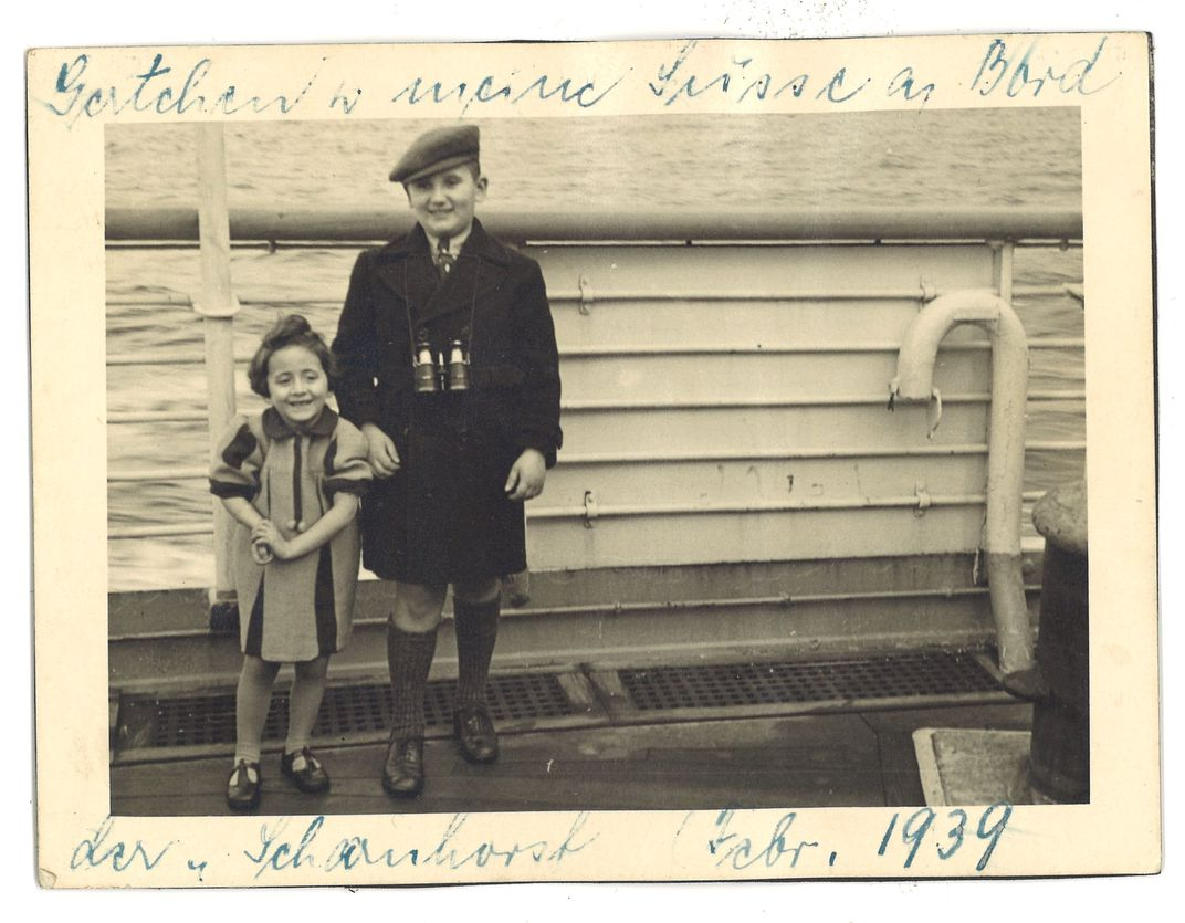 A yellowed image of a small girl and an older boy, smiling on the deck of a ship; dated 1939