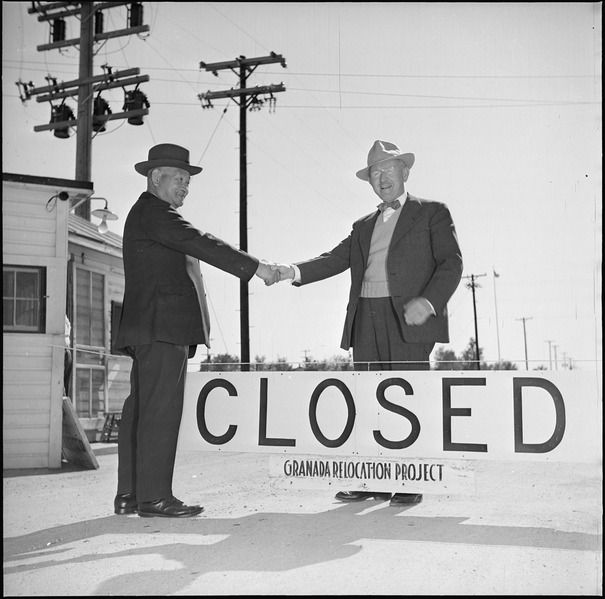 "A black and white photo shows two men shaking hands in front of a sign that reads ""Closed-Granada Relocation Project""."