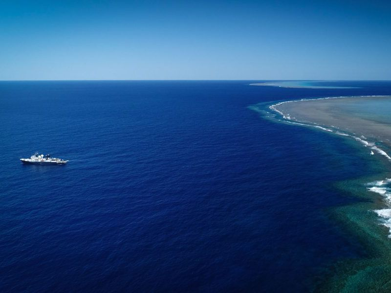 A photo taken from high above (likely by drone) shows the vast, bright blue ocean. The research vessel is on the left side. A long green and beige stretch of shallow coral reefs is on the right side. The horizon, where the deep blue ocean meets the lighte
