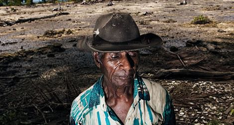 Posakei Pongap, a Manus islander, in front of a field ruined by salinization.