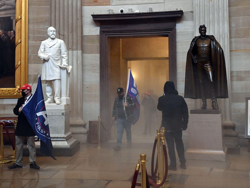 Two men carrying large blue flags - the first words of KEEP AMERICA GREAT appear in one - walk into the corridor flanked by two statues of men and huge Trumbull paintings in gilded frames, surrounded by hazy gas on the floor