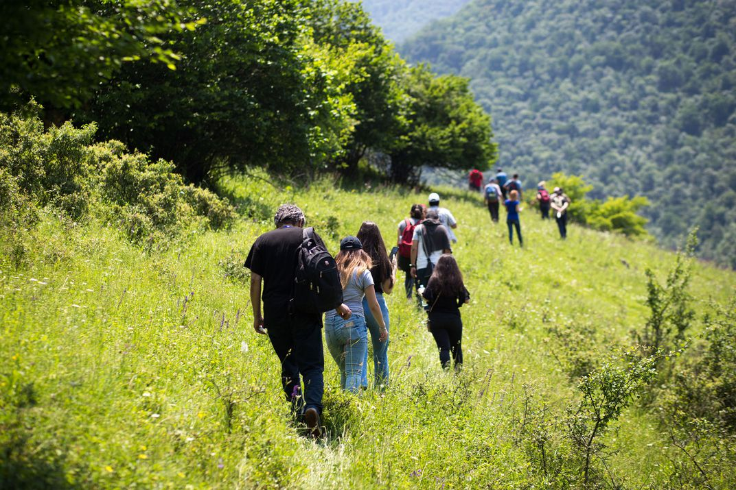 A group of hikers walk through a field towards a mountain, their backs facing away from the camera.