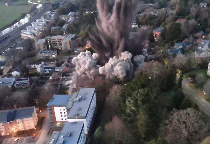 An aerial view of a huge explosion taking place in the middle of a neighborhood, with dust and smoke clouds emerging from buildings and surrounded by green trees