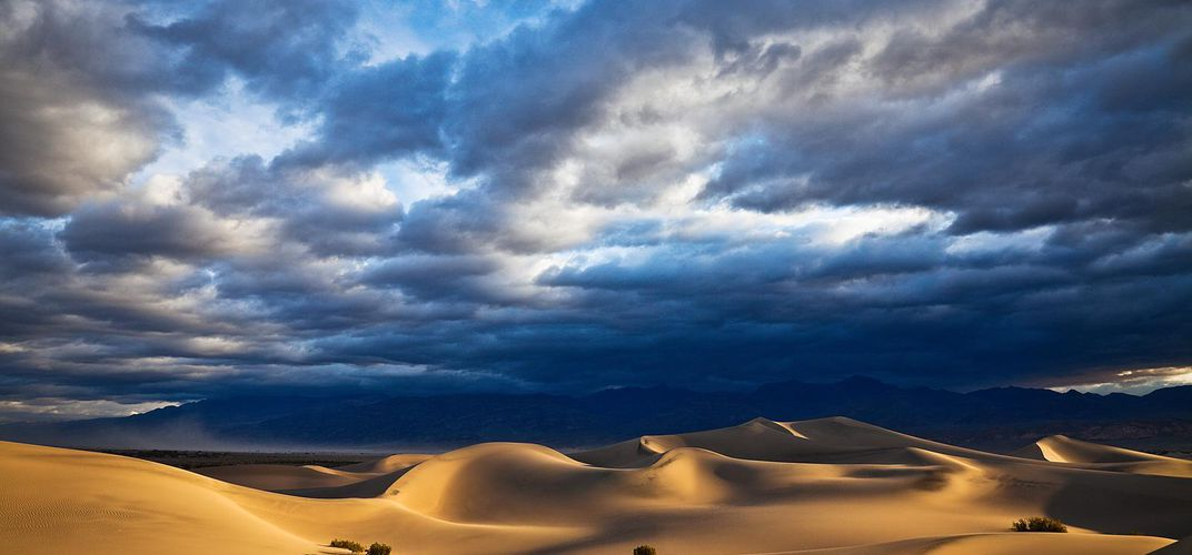 Rolling sand dunes under stormy skies in Death Valley. Credit: Greg Clure