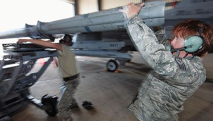 Staff Sergeant Michelle Torrey, right, with Master Sergeant Brett Kitzman load an AIM-120 missile onto an F-16.