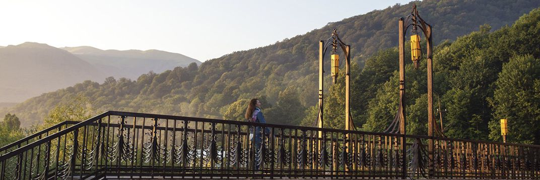 A woman stands on an ornate bridge with two hanging light fixtures in the middle. Behind her tree covered mountains recede into the distance.
