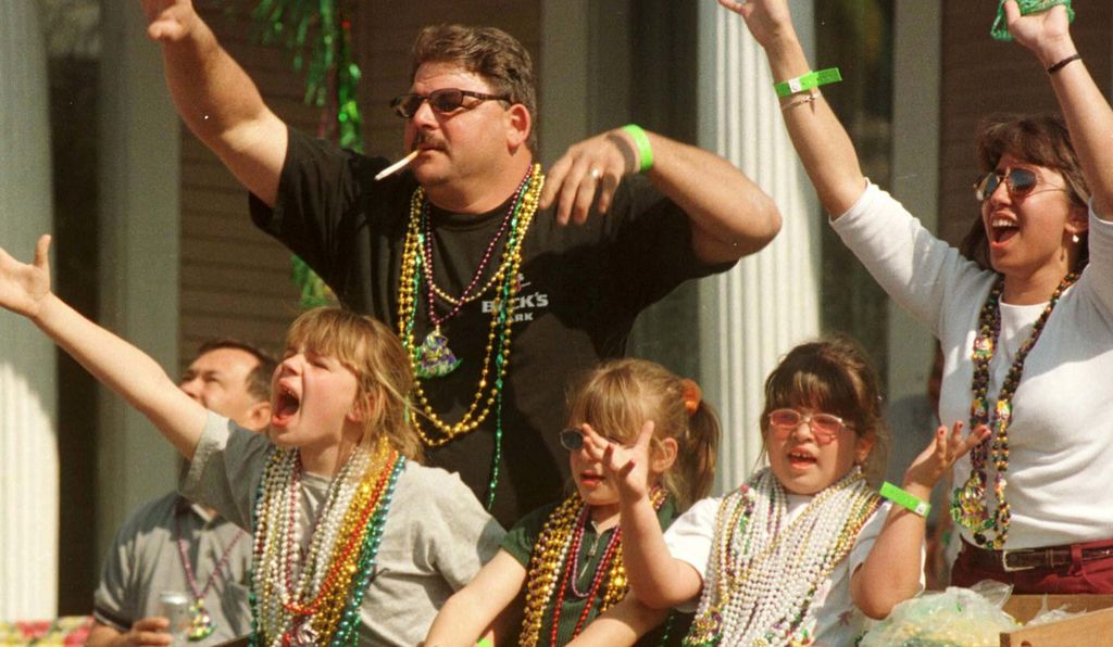 A family catches Mardi Gras beads during the Krewe of Thoth parade down St. Charles Avenue in 2000.