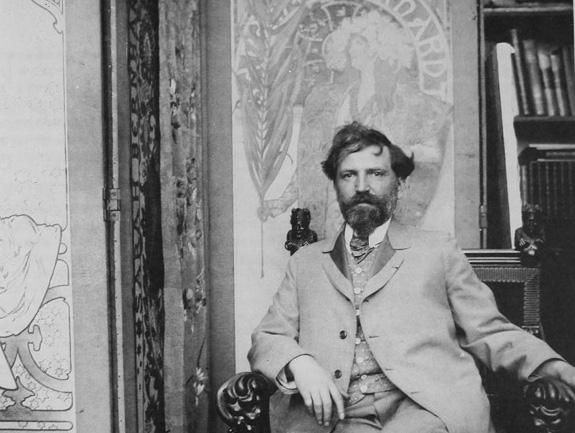 Alphonse Mucha in front of his first poster for Sarah Bernhardt