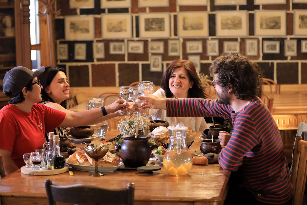 A group of five, smiling people sit together at a wooden table. Their glasses are raised, going in for a toast.