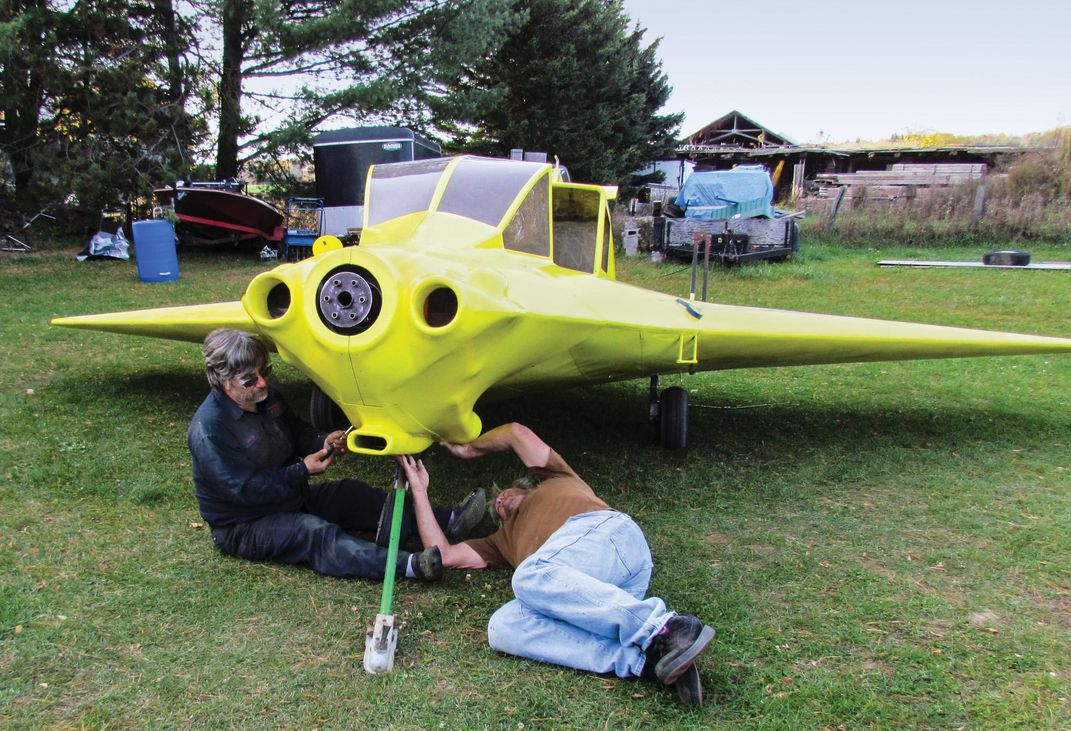 two men working on a chartreuse Delta