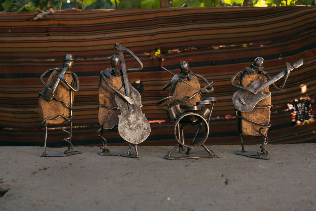 Four metal sculptures of human figures playing instruments are positioned next to each other.