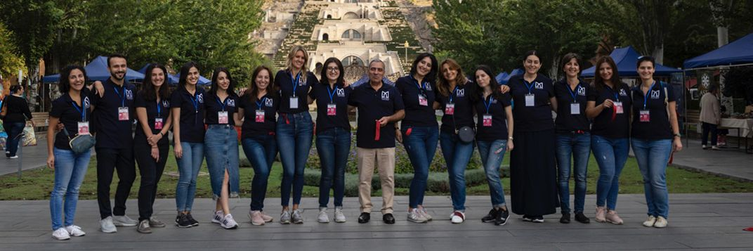 My Armenia Program staff stand with their arms around each other at the opening of the My Handmade Armenia Festival. Behind the group are the white stairs of Casfejian Center for the Arts.