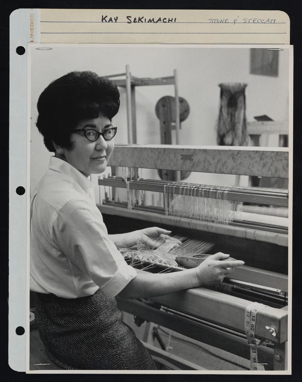 Black and white image of a woman sitting at a loom, looking at the camera