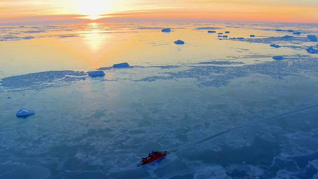 A ship sails through ice sheets on the ocean as the sun sets.