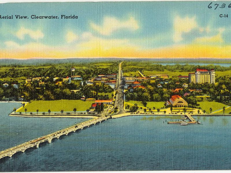 An aerial view of the city on the bay, with blue water in foreground and a bridge extending to the left