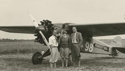 Three-quarter left front view of Cessna BW-5 (r/n C6623, National Air Races race no. 98) on the ground, possibly at Roosevelt Field, Long Island, New York, circa September 1928. Posed standing beside nose of aircraft are pilot Francis D.