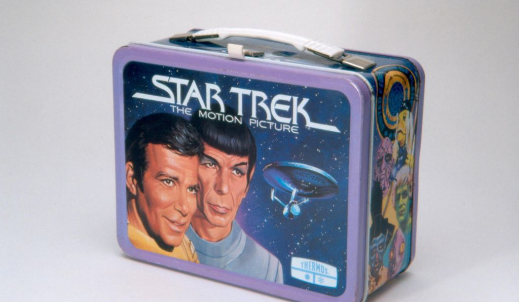 This metal lunch box was manufactured by Thermos in 1979. The lunch box features cartoon images of Captain Kirk and Mr. Spock on the front lid. The back shows the image of Captain Kirk, Mr. Spock, and Dr. Bones McCoy inside the USS Enterprise. Various show scenes along sides. White plastic handle and snap. This lunch box was based on Star Trek: The Motion Picture, the first Star Trek feature film released in 1979.