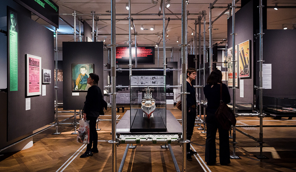 The display is framed as a makeshift construction site, with scaffolding enclosing and supporting the items on view