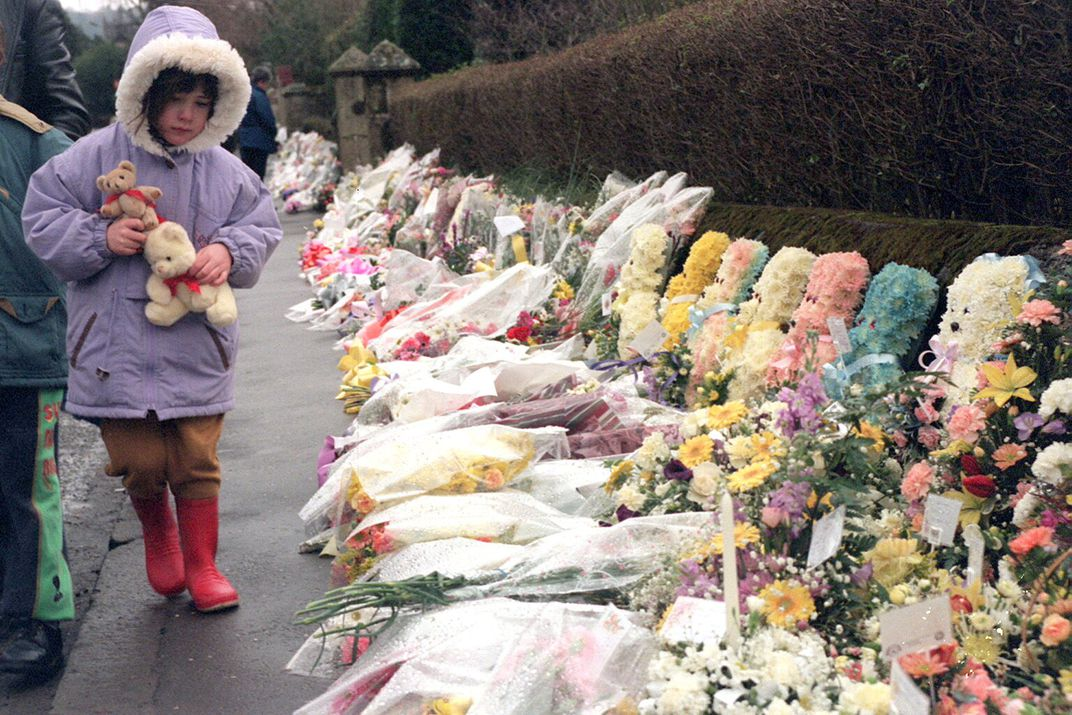 A young girl walks past a row of flowers honoring her murdered classmates and teacher