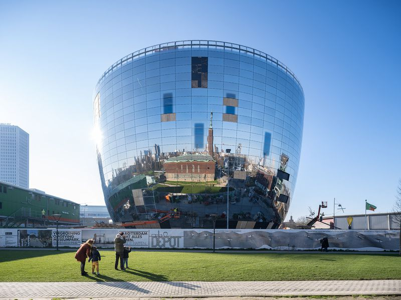A large building shaped like a sphere with a flat top, with mirrors all around the building's surface that reflect the blue sky and white clouds