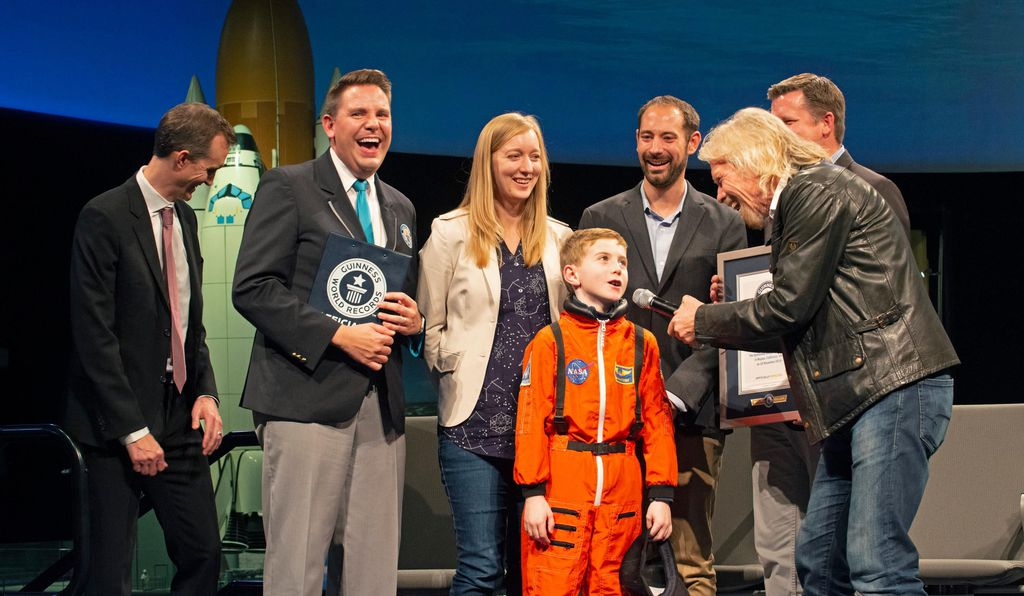 Wearing his orange space suit, 8-year-old George Madden, who hopes to ride into space, met with Sir Richard Branson and others at the National Air and Space Museum on the day Virgin Galactic donated a hybrid engine to the Smithsonian's collections.