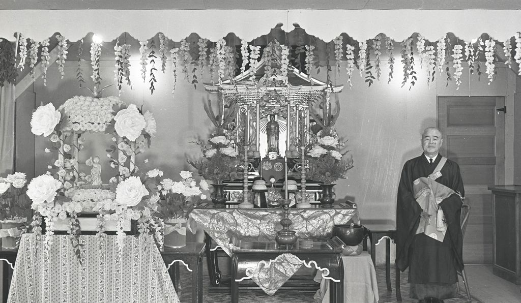 Japanese-American Rinban Kankai Izuhara at the altar in the Buddhist church at Heart Mountain.