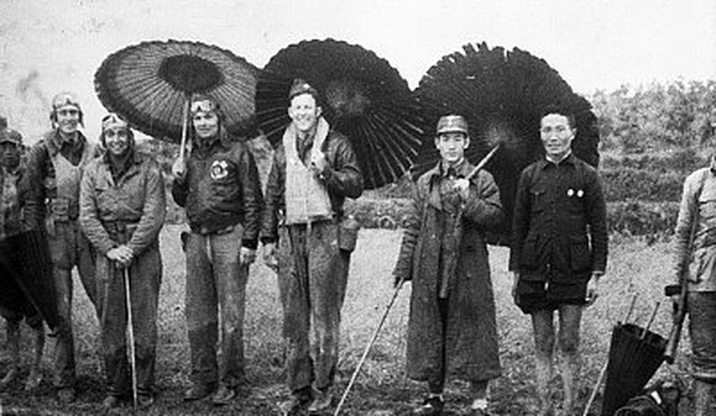Four of the American fliers who raided Tokyo grin out from beneath Chinese umbrellas that they borrowed.